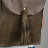 olive brown leather backpack with adjustable buckle straps and a tassel at the flap closure