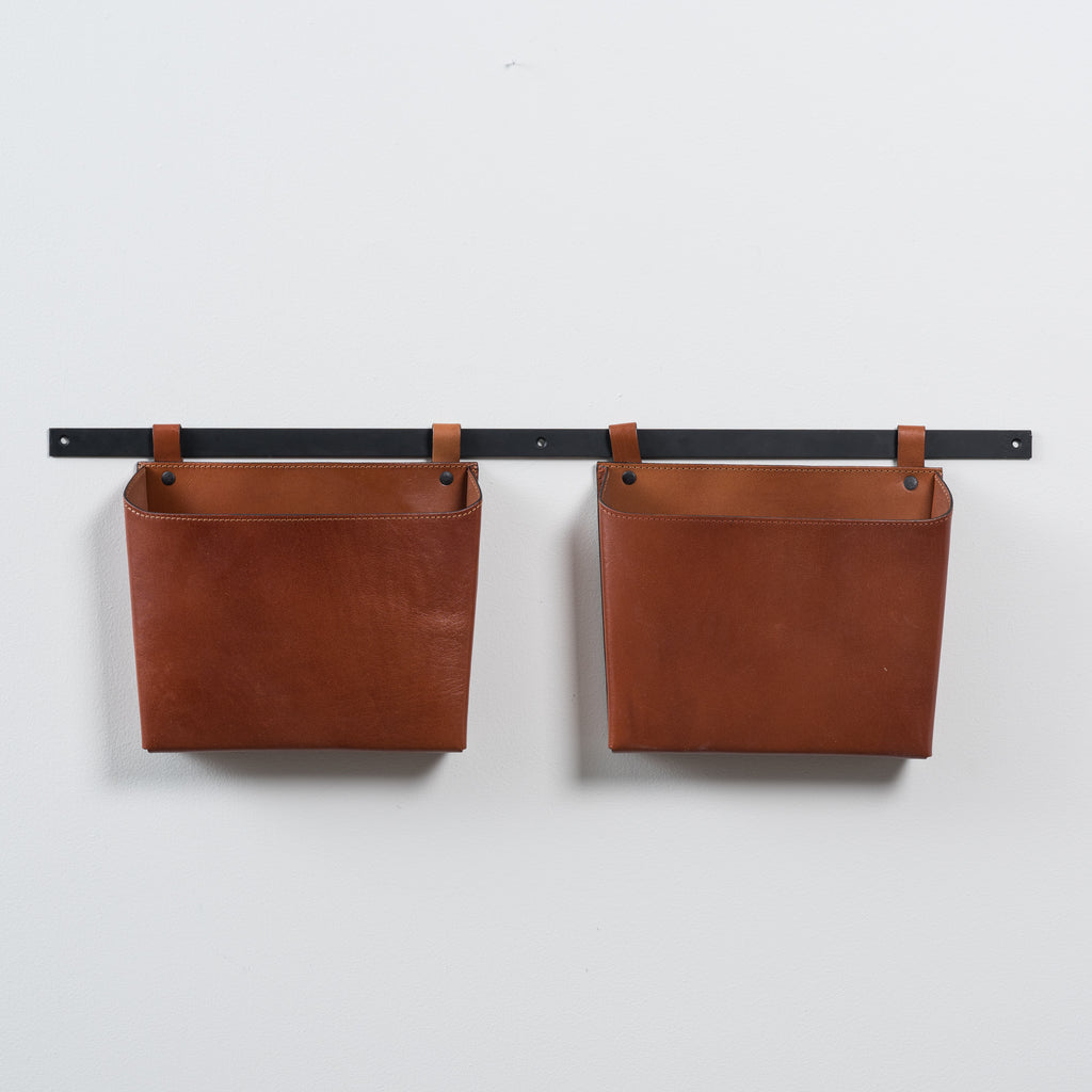 double leather wall organizer on black metal bar