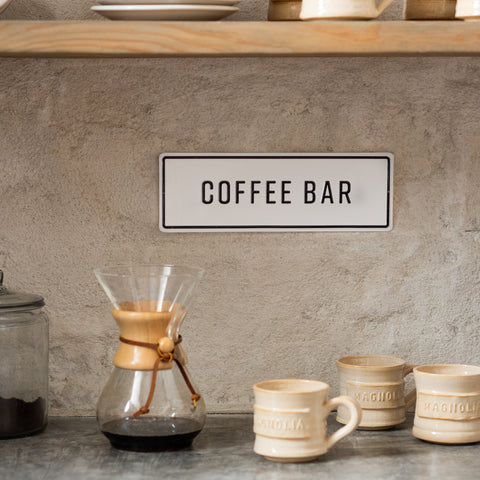"white and black metal embossed sign that reads ""coffee bar"""
