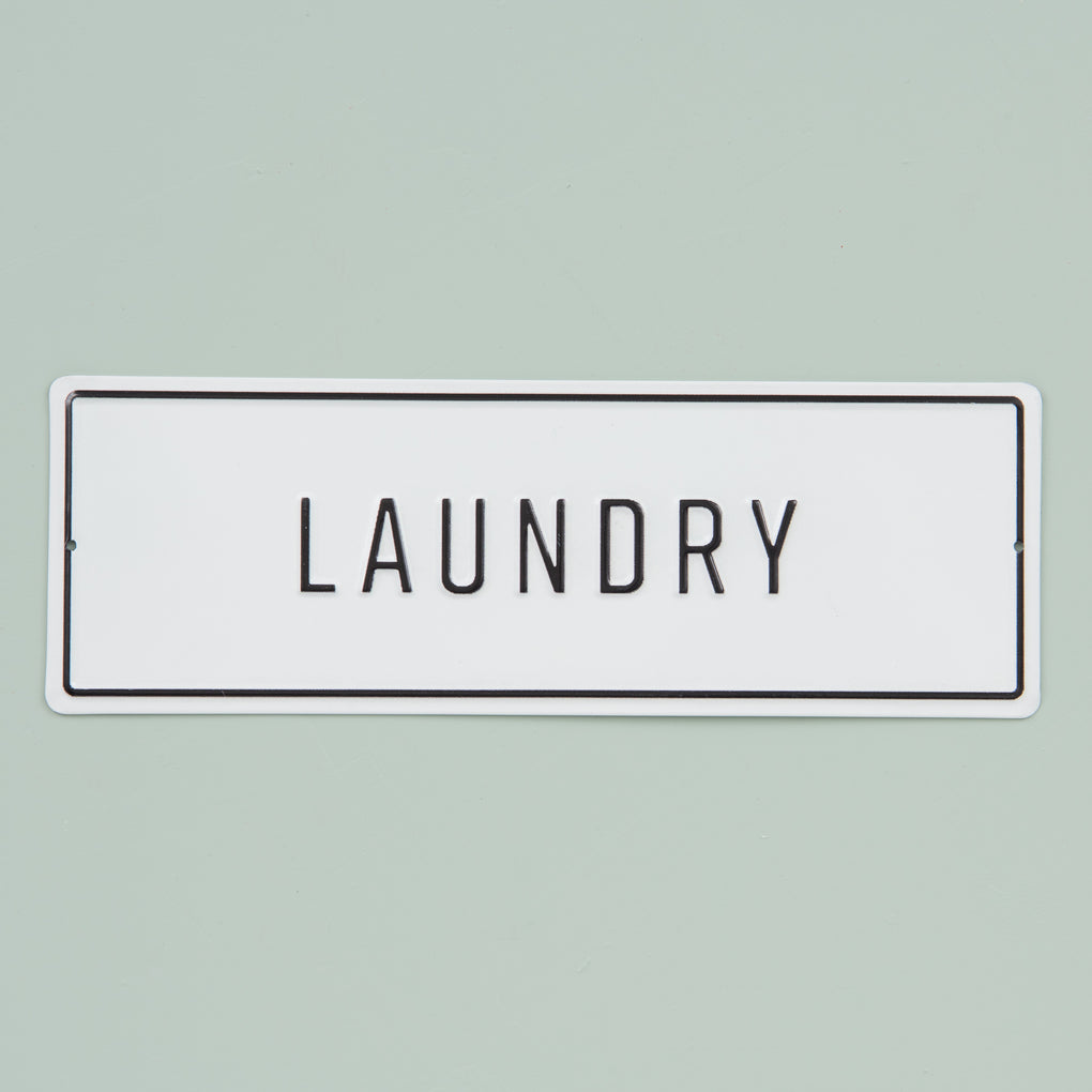 "white and black metal embossed sign that reads ""laundry"""