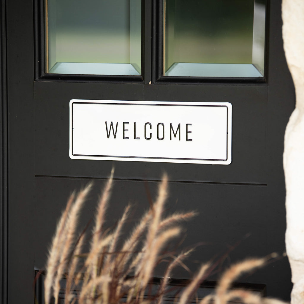 "white and black metal embossed sign that reads ""welcome"""