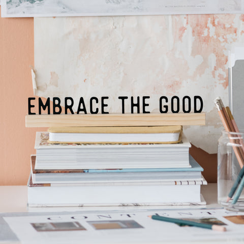 "acrylic quote sign with wooden stand that says ""embrace the good"""