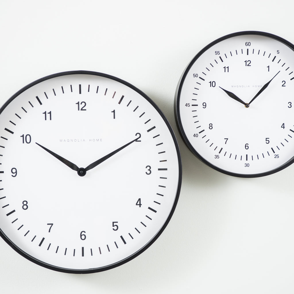 black metal wall clock with white face and black numbers
