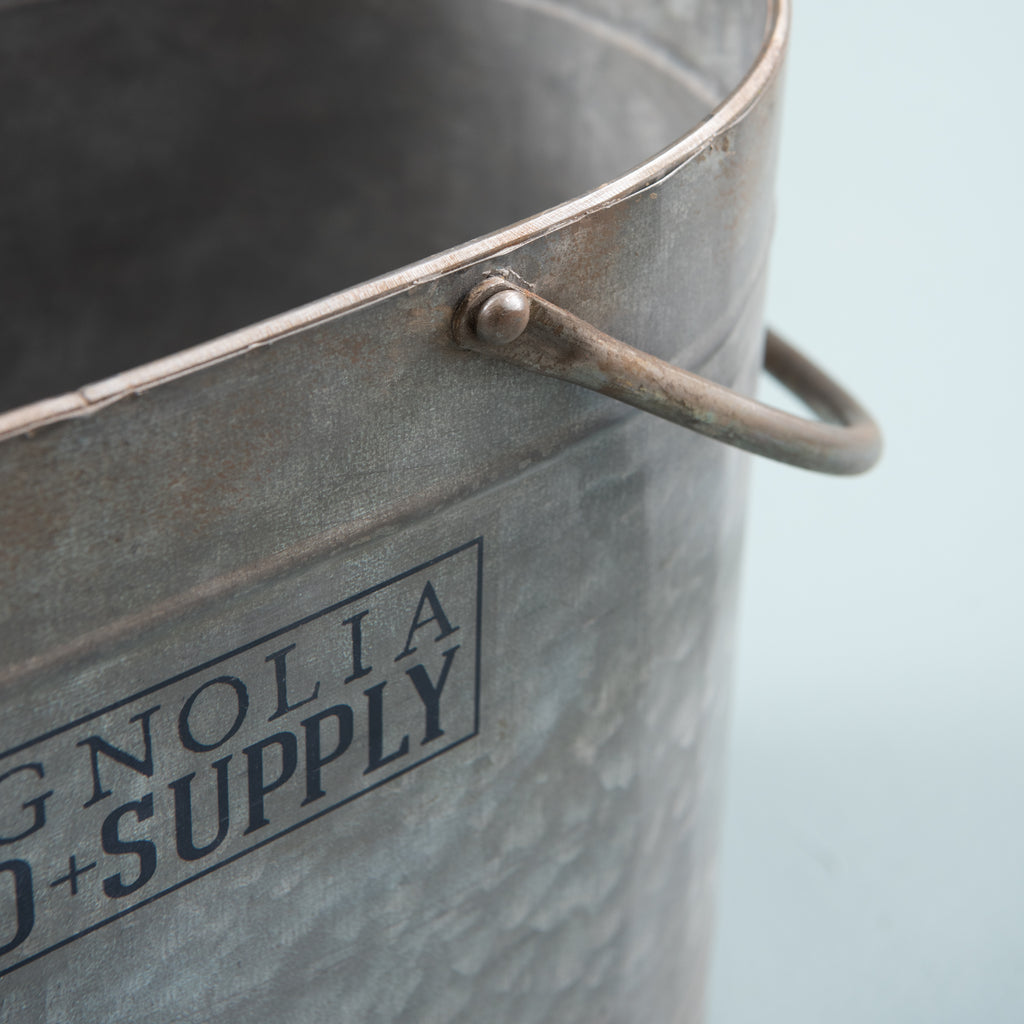 oval galvanized metal bucket with Magnolia Seed and Supply logo on the side