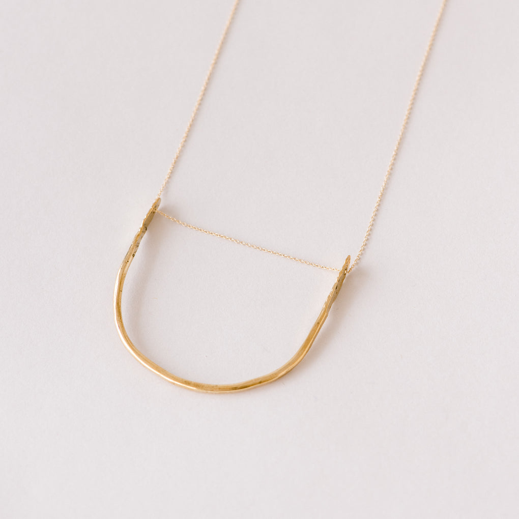 gold arched pendant necklace
