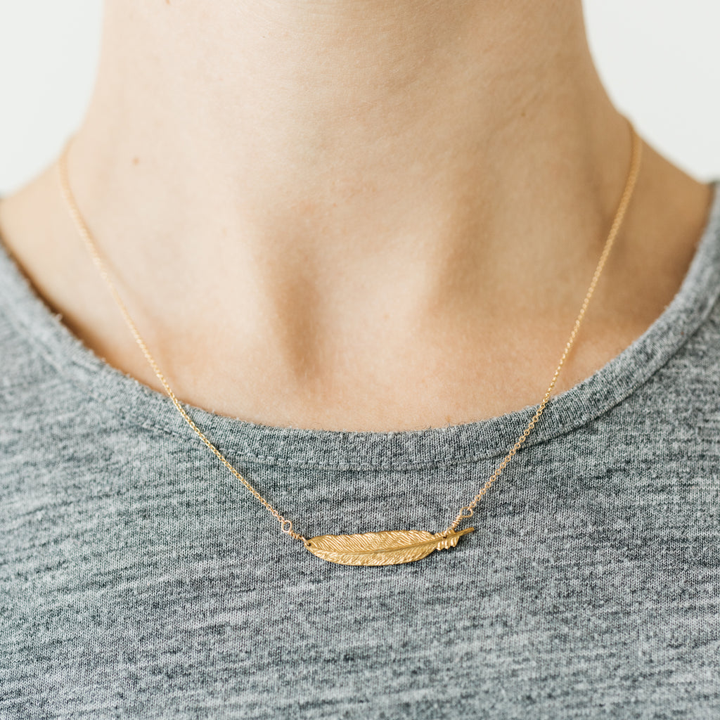 gold necklace with feather pendant