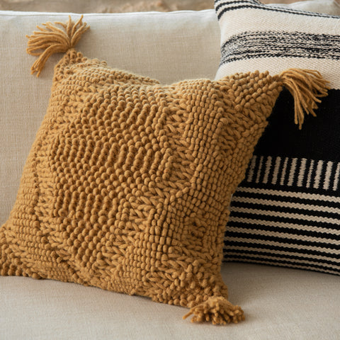 square gold pillow with woven texture and corner tassels