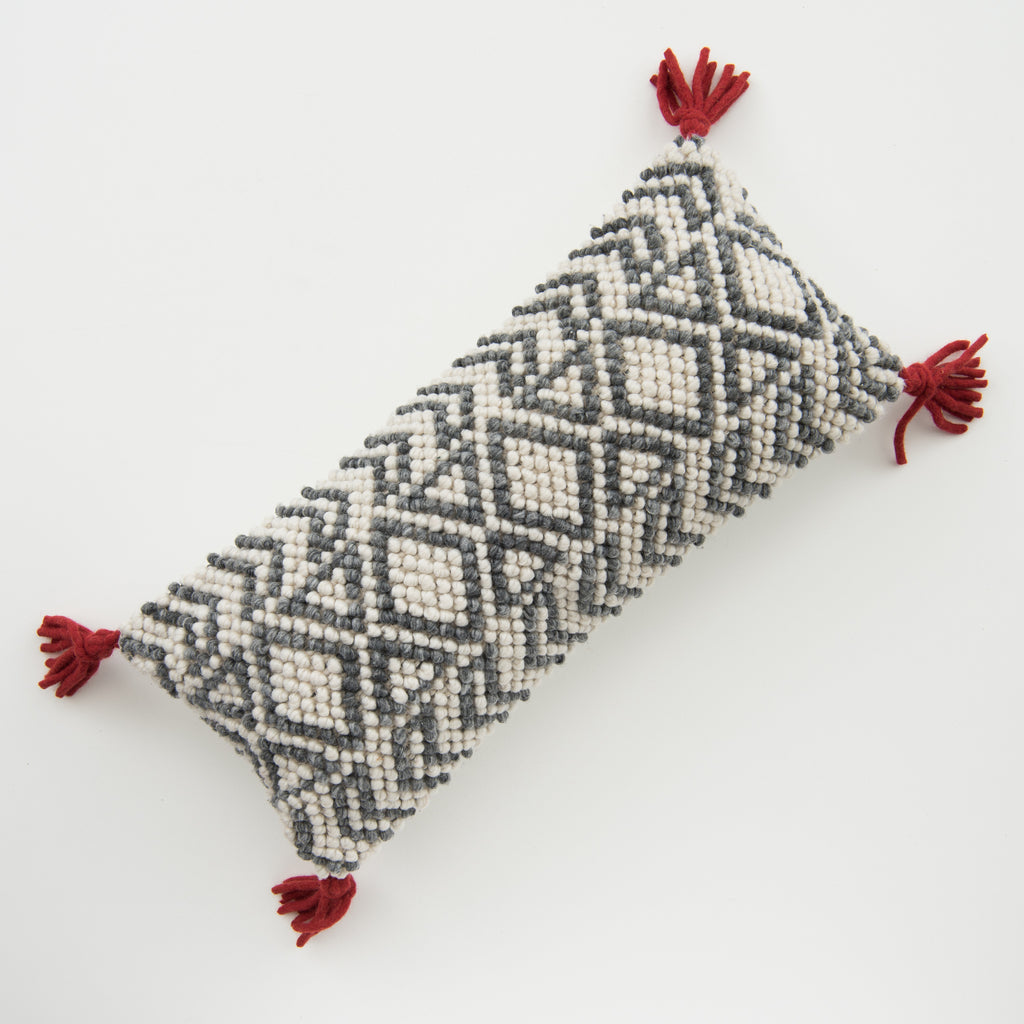 grey and white geometric patterned pillow with red tassels