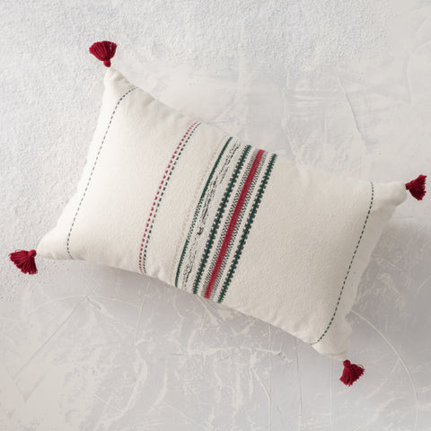 cream lumbar pillow with red and green stripes and red corner tassels