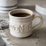 white handthrown ceramic mug with original Magnolia logo embossed on side
