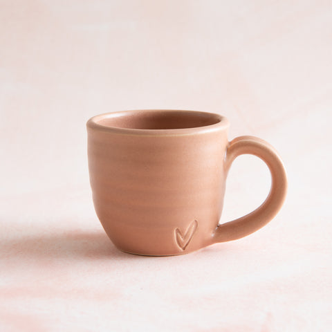 muted pink hand thrown mug with heart stamped into side