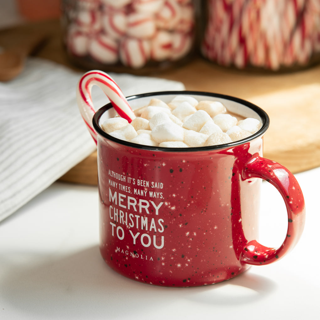 "red christmas mug with white speckles and lyrics ""although it's been said many times, many ways, merry christmas to you"""