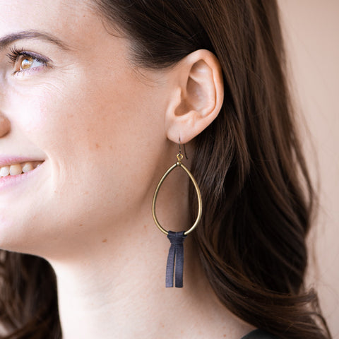 brass teardrop shaped hoop earring with black leather tassel hanging from bottom