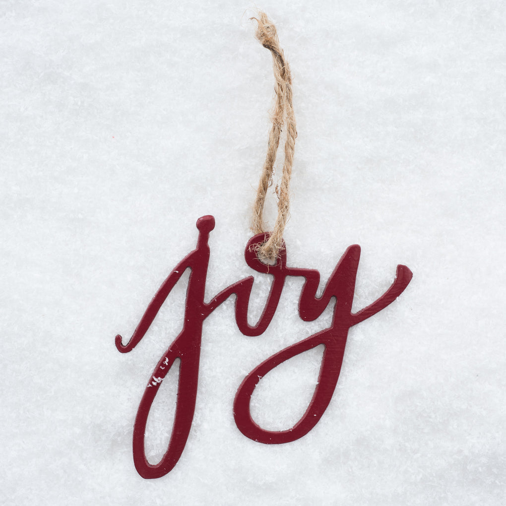 "red script ornament that says ""joy"""