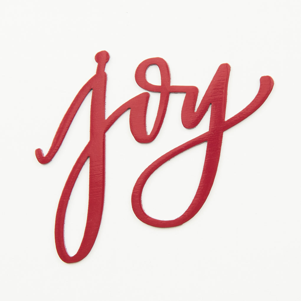 "red script metal wall sign that says ""joy"""