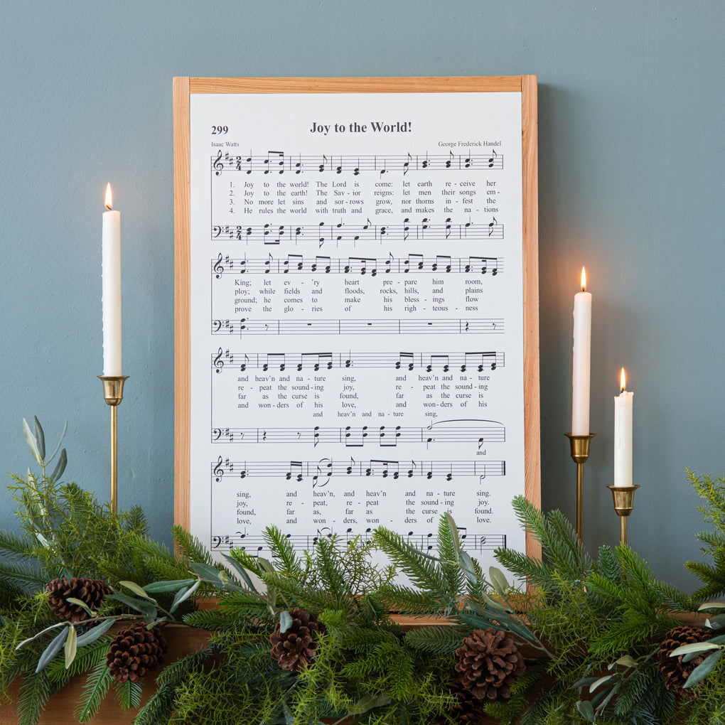 "white wooden sheet music wall decor with lyrics of ""joy to the world"""