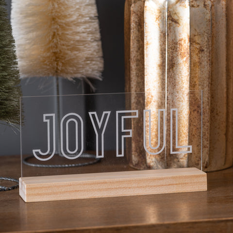 "clear acrylic sign with expression reading ""joyful"" on wooden stand"