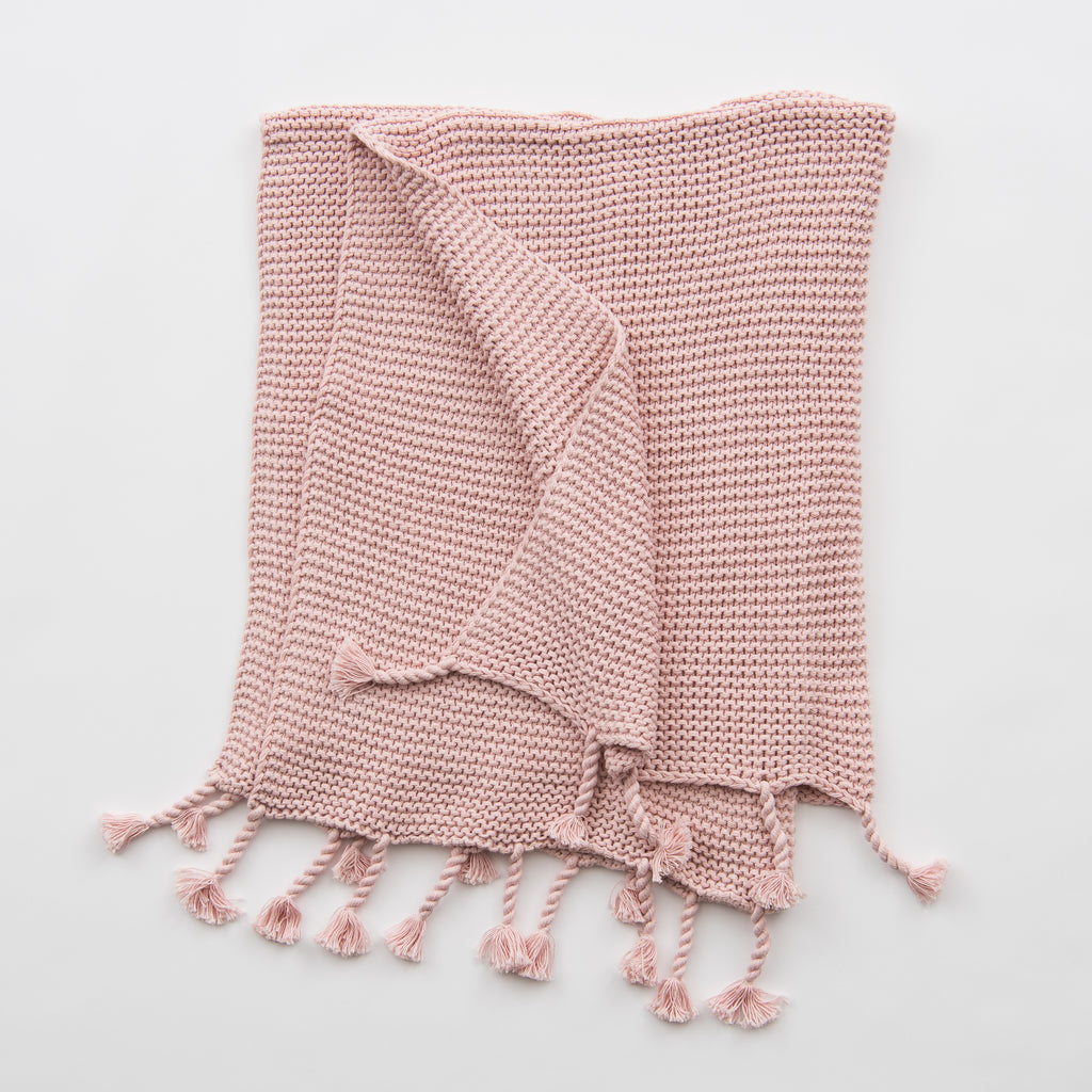 light pink knit throw blanket with tassels