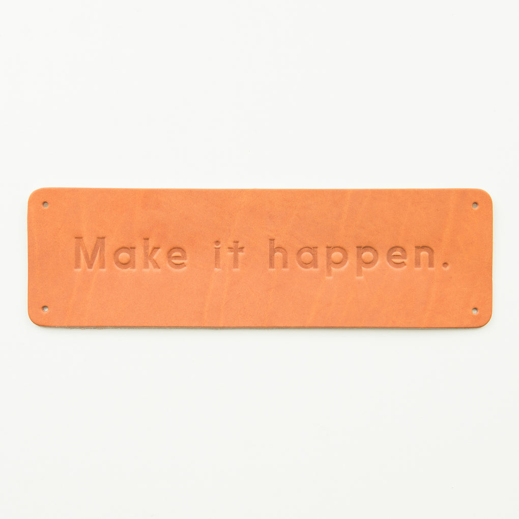 "leather wall sign that reads ""make it happen"""