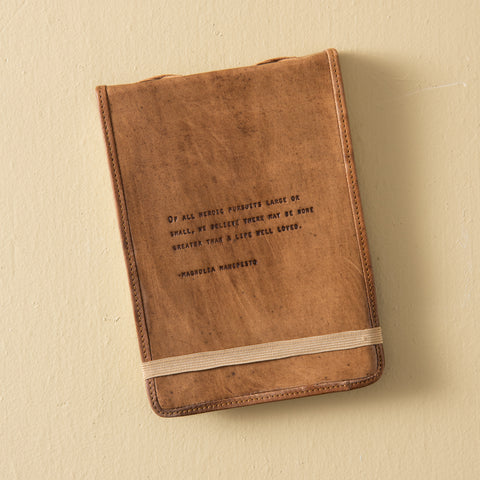 leather journal with line from Mangolia Manifesto embossed on cover