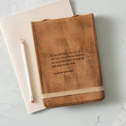 leather journal with excerpt from magnolia manifesto embossed on the cover