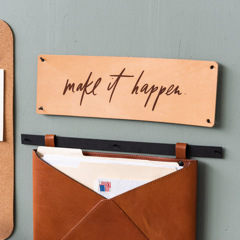 "light colored leather sign with phrase ""make it happen"" in modern script"