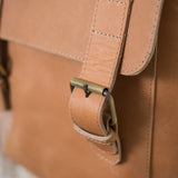 medium toned leather backpack with buckle closures