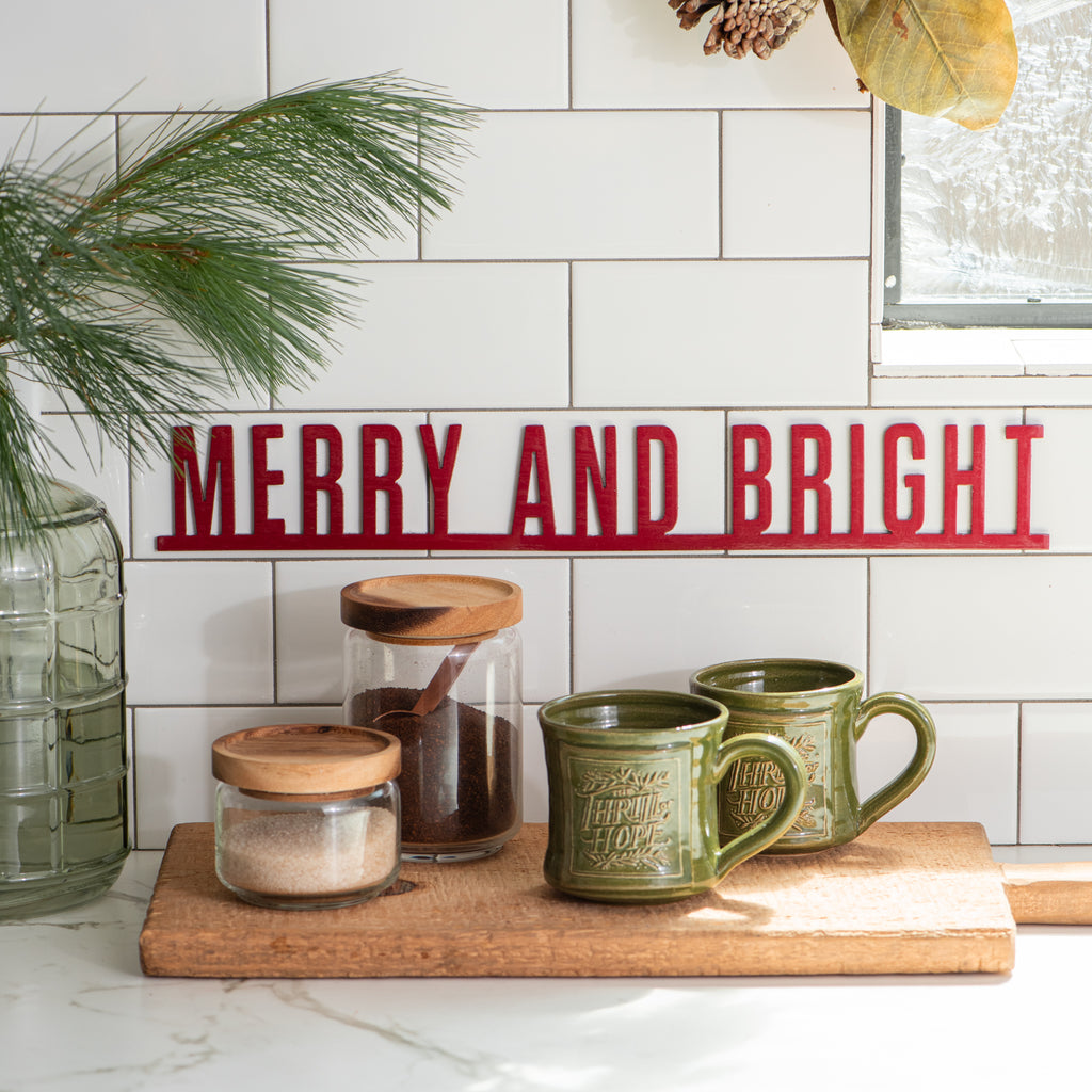"red metal wall expression of ""merry and bright"""