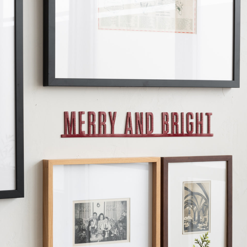 "red metal wall expression reading ""merry and bright"""