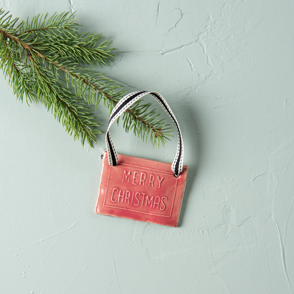 "red ceramic christmas ornament that says ""merry christmas"""