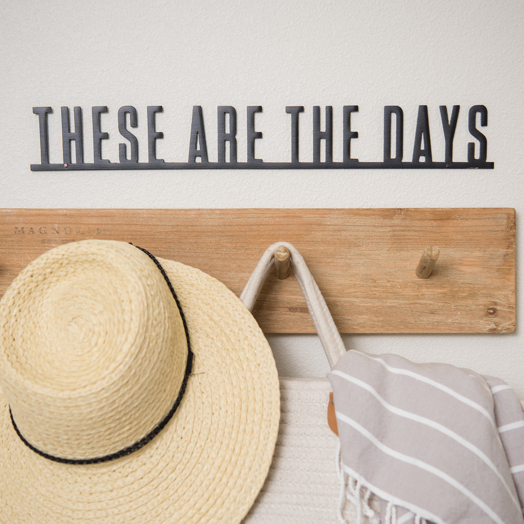 "metal wall expression that reads ""these are the days"""