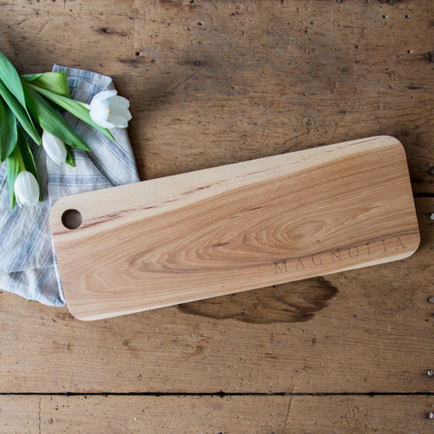 wooden cutting board with magnolia logo embossed in corner