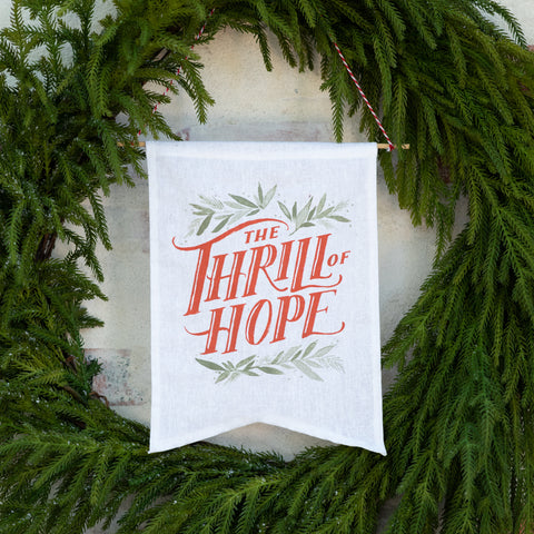 "small white banner with saying ""the thrill of hope"" in red"