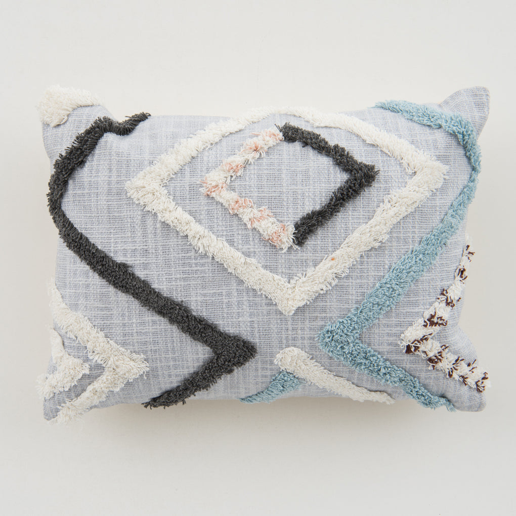 blue pillow with white and grey diamond detail