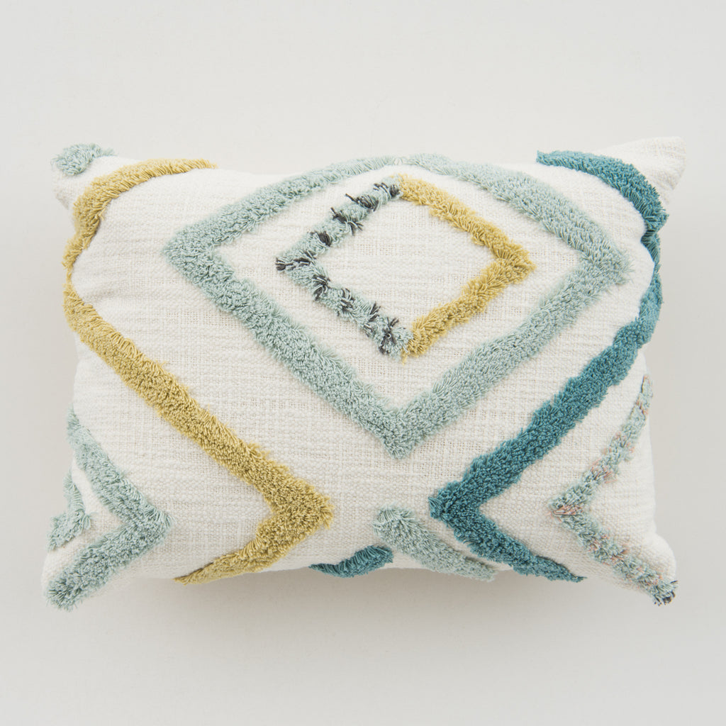 white pillow with yellow and teal diamond detail