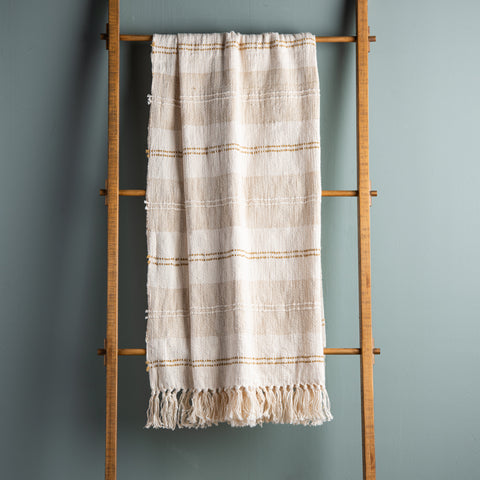 cream decorative fringed throw with tan and mustard stripes