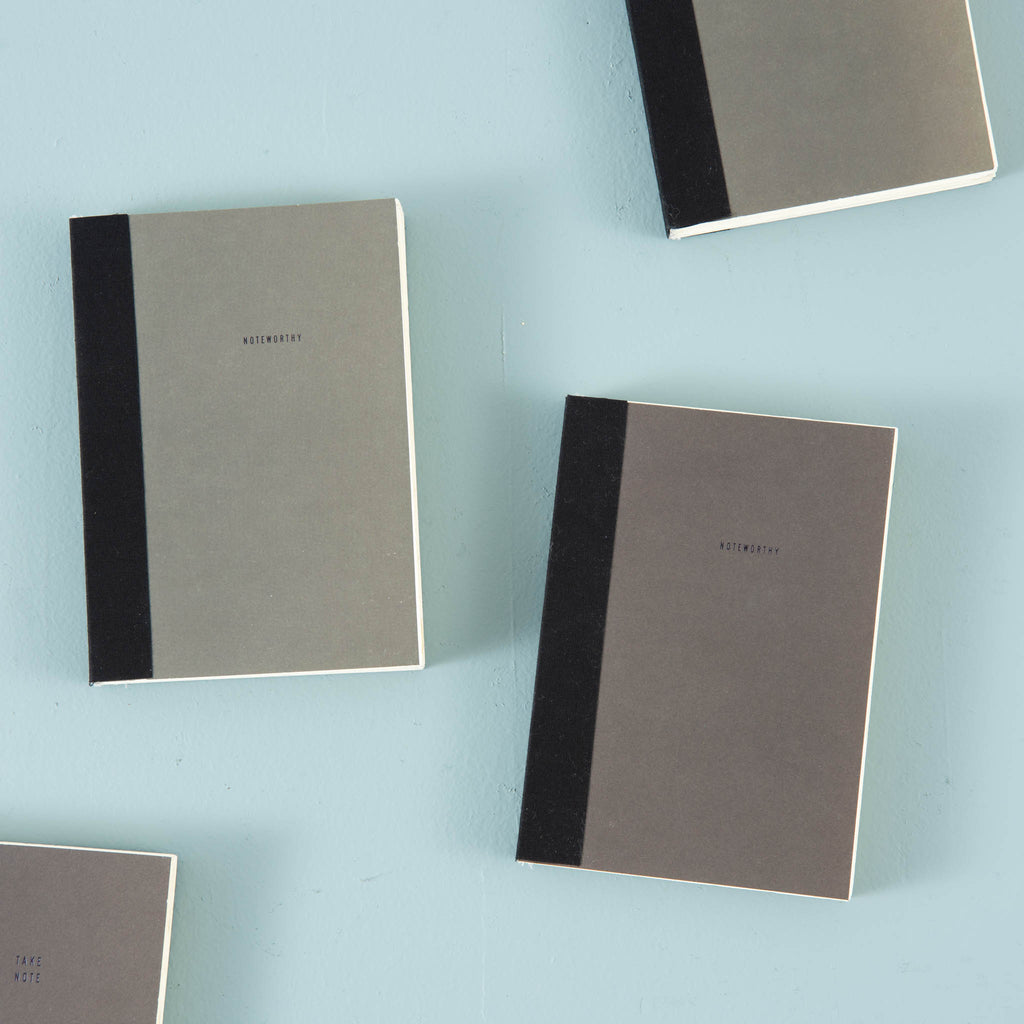"grey magnolia notebook that says ""noteworthy"" on the cover"