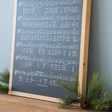 "black wooden sheet music wall sign with lyrics to ""o holy night"" in white"