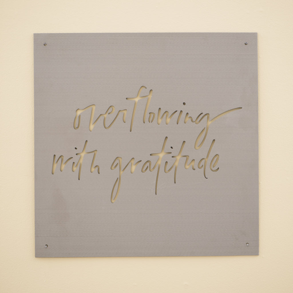 "metal quote sign that reads ""overflowing with gratitude"""