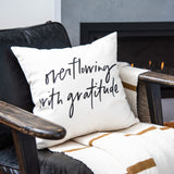 "white throw pillow with black writing that says ""overflowing with gratitude"""