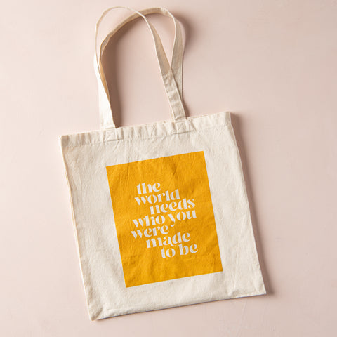 "cream canvas tote with handles and yellow block quote reading ""the world needs who you were made to be"""