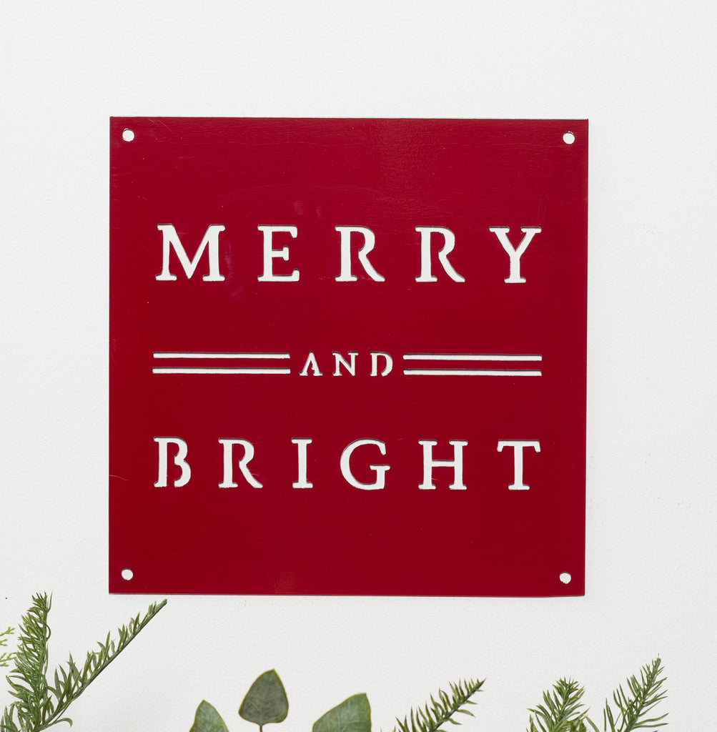 red metal quote sign that says merry and bright