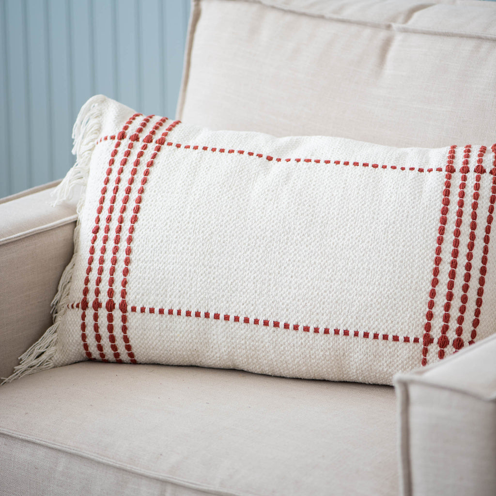cream rectangular pillow with red stitching and cream fringe ends