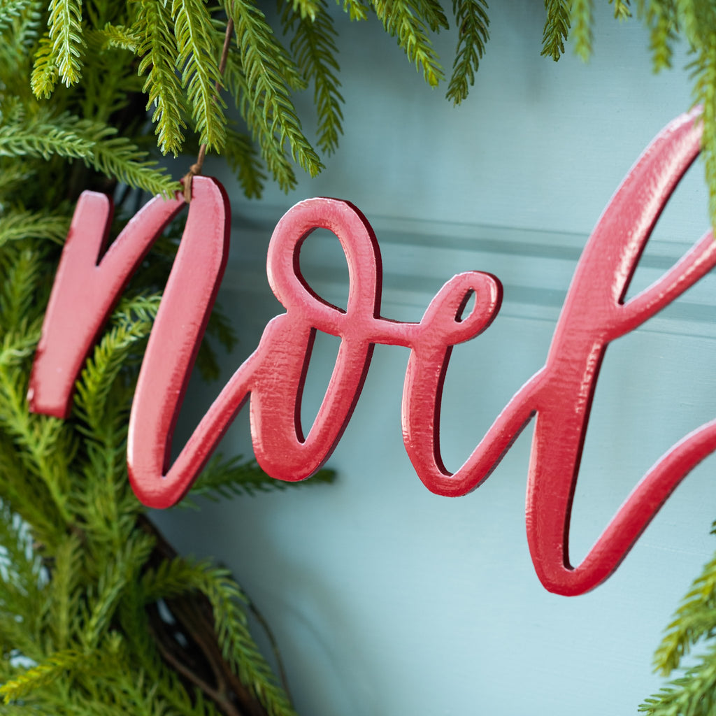 "red metal script wall expression reading ""NOEL"""