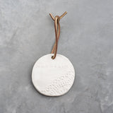 ceramic circle ornament with lace detail and magnolia logo