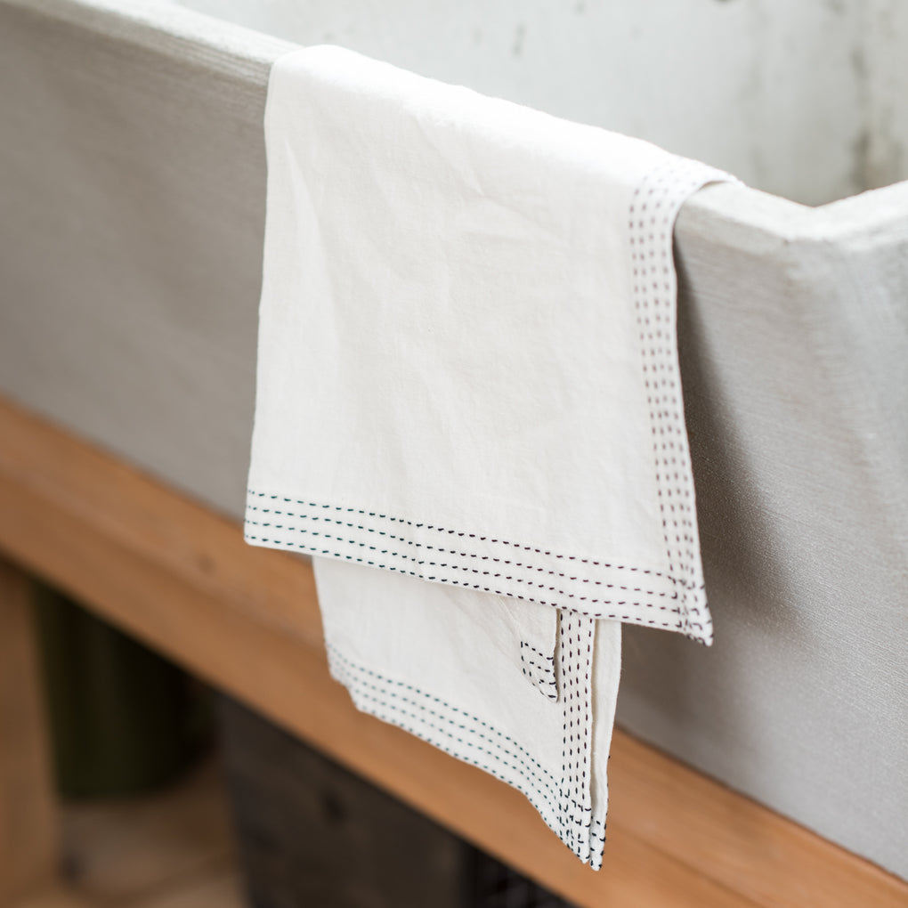 white cloth tea towels with black outer stitching