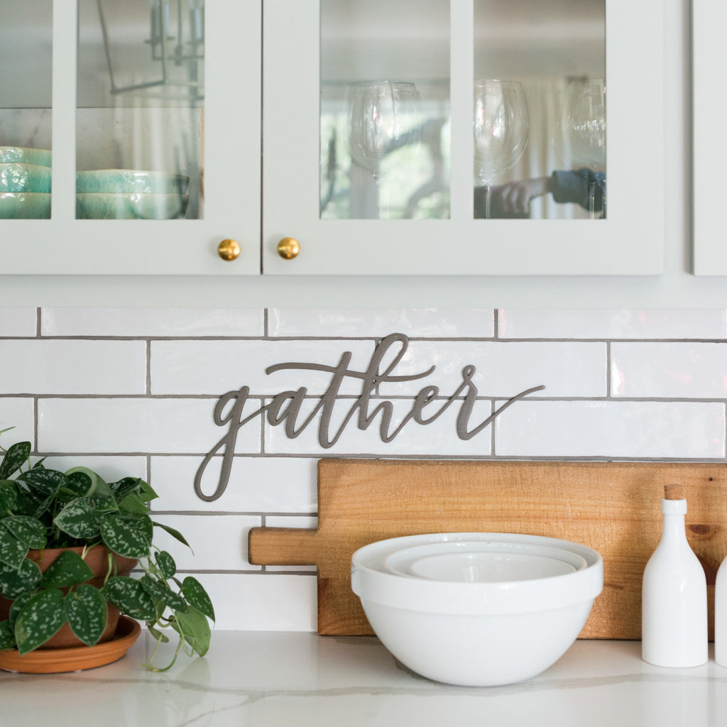"metal script wall expression that says ""gather"""