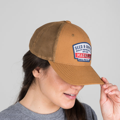 camel colored seed and supply badge hat