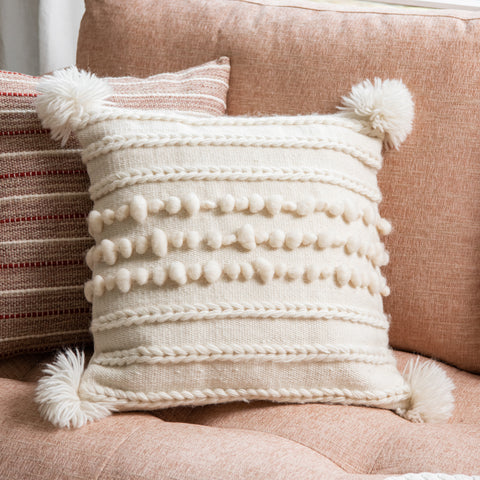 white pillow with tassels,  pom poms, and raised stripe detail