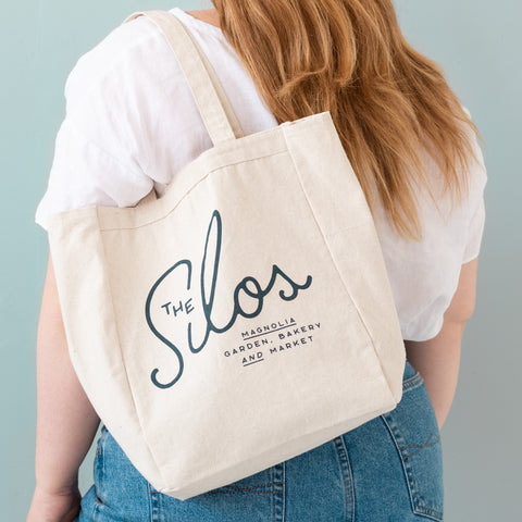 "white canvas tote with new Magnolia logo that reads ""The Silos: Magnolia Garden, Bakery, and Market"""